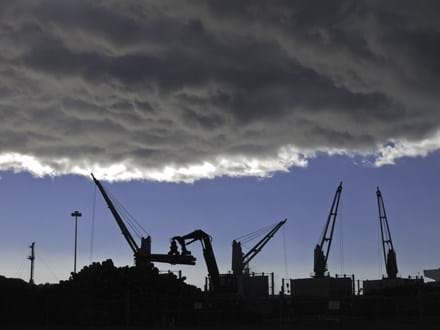 Storm cloud over silhouettes of cranes lifting logs to be shipped from seaport of Astoria, Oregon-2.jpeg